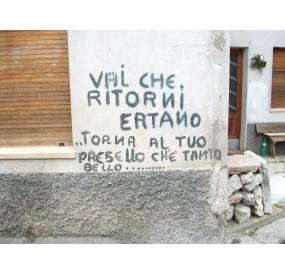 Old graffiti regarding the disaster, in Erto town center